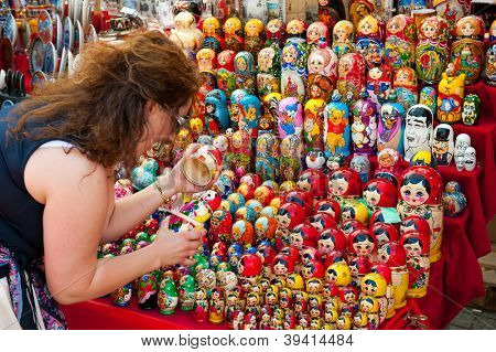 MOSCOW - JULY 26: Unidentified tourists choose a Matryoshka at the gift shop on July 26, 2012 in Moscow on Red Square. Nesting dolls are the most popular souvenirs from Russia