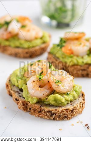 Bruschetta With Avocado Cream And Shrimps On White Marble Background, Closeup View. Appetizer Or Sna