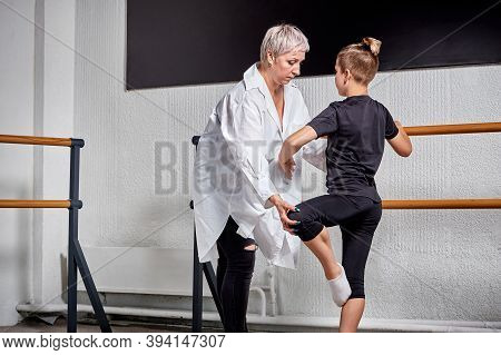 A Young Woman Teacher Teaches A Young Man Ballet. Ballet School.