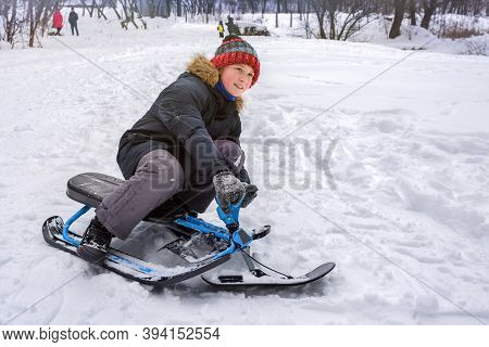 A Teenager Boy Is Sitting On A Sledge In A Snowy Park, A Close-up. Winter.
