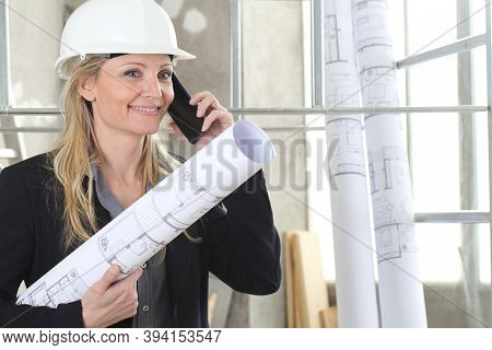 Smiling Woman Architect Or Construction Engineer Talk On The Mobile Phone Wear Helmet And Holds Blue