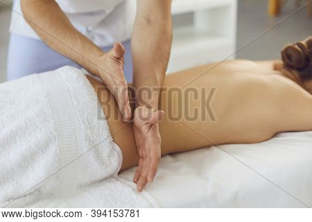 Hands Of A Male Masseur Knead The Muscles Of A Womans Back In A Massage Parlor.