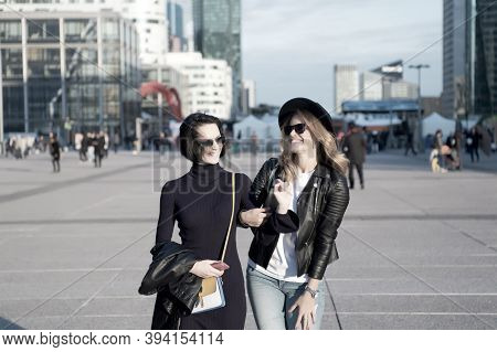 Happy Women Walk In Business District Of La Defense, Paris. Girls Smile In Fashionable Clothes On Su
