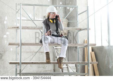 Woman Worker Builder Sitting On Scaffolding To Coffee Break Talking On Mobile Phone, Wearing Helmet,