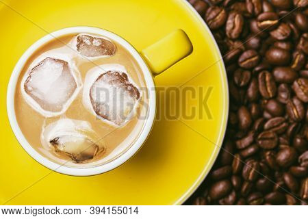 Ice Coffee Top View. Frozen Latte With Ice Cubes. Yellow Ceramic Cup On Yellow Ceramic Plate. Coffee