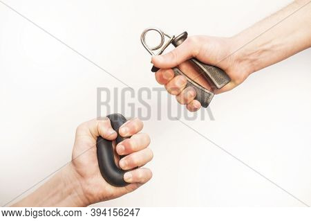 Two Men's Hands With Hand Expander. Hand Grip Strengthening Tool. Expander