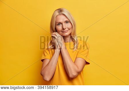 Portrait Of Good Looking Senior Woman Looks Confidently At Camera Leans At Hands Dressed In Casual Y