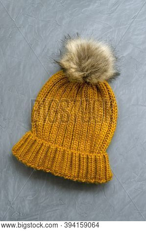 Small Cute Knitted Warm Woolen Hat With A Mustard-colored Fur Pom-pom On A Gray Concrete Background