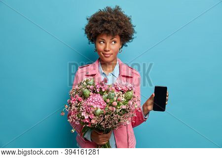 Pretty Afro American Woman With Fresh Spring Flowers Bouquet, Holds New Mobile Phone And Looks Myste