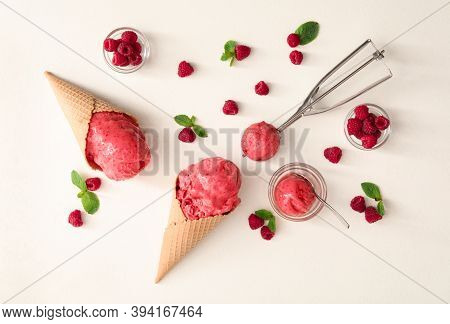 Flat Lay Composition With Delicious Pink Ice Cream In Wafer Cones And Raspberries On White Table
