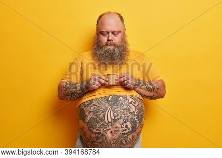 Serious Bearded Man With Big Tummy, Tattooed Arms And Belly, Holds Very Small Carton Cup Of Coffee C
