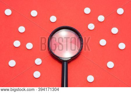 Black Magnifying Glass Is On Red Background Surrounded By White Pills As Ornament Polka Dots. Medica