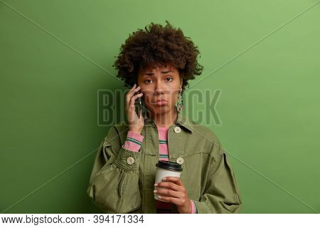 Photo Of Dissatisfied Unhappy Woman With Afro Hair Has Unpleasant Phone Conversation, Keeps Mobile P