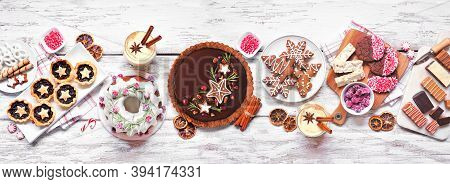 Various Christmas Holiday Desserts And Sweets. Overhead View Table Scene On A White Wood Banner Back