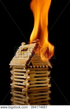 Burning house from matches. Property insurance, risky investment concept. Isolated symbol on black background.