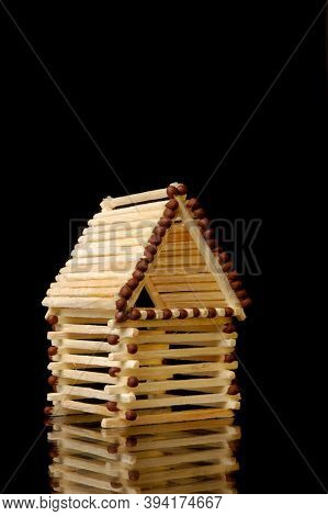 House made from matches. Risky investment concept. Isolated symbol on black background.