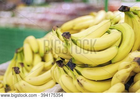 Pile Of Bananas In Hypermarket Against Blurred Shop Shelves