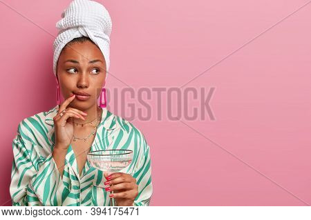 Thoughful Lady Enjoys Drinking Martini Cocktail After Taking Shower, Looks Aside, Has Well Cared Com