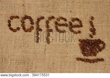 Conceptual artistic pattern of a cup of coffee made from coffee beans on rustic burlap background