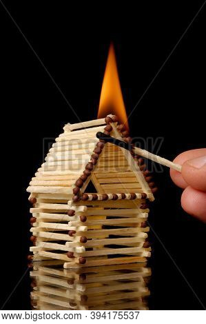 Hand with a burning match putting a house on fire. Property insurance, risky investment concept. Isolated symbol on black background.