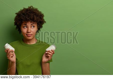 Pensive Beautiful Woman Cares About Health, Holds Two Glass Bottles Of Healty Nutrient Fresh Organic