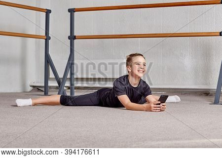 A Young Man Performs The Splits, Holds The Phone In His Hands And Smiles.