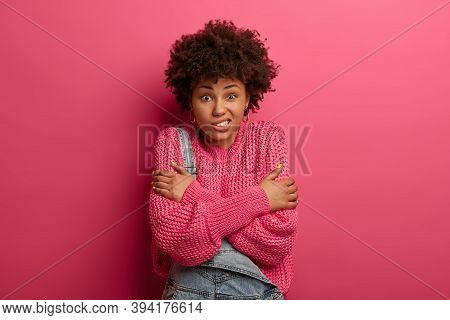 Studio Shot Of Good Looking Ethnic Curly Haired Woman Trembles From Feeling Cold, Crosses Arms Over