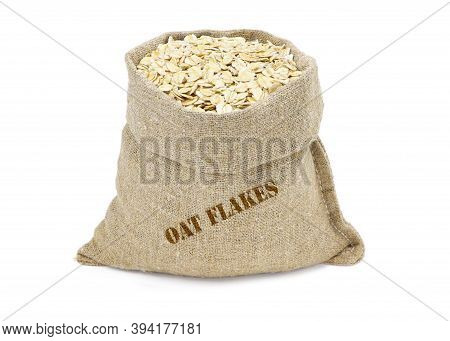 Oat Flakes In A Sack Isolated On A White Background. Oat Flakes In Burlap Sack. Oat Flakes In Jute B