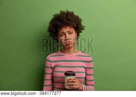 Photo Of Displeased Gloomy Curly Woman Feels Tired And Exhausted, Holds Takeaway Coffee, Sulks And H
