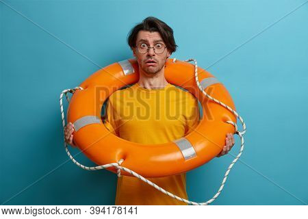 Fearful Man Afraids Of Swimming In Deep Sea, Poses With Inflated Lifebuoy, Listens Advice Of Instruc