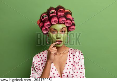 Serious Looking Lady Wears Casual Robe And Hair Rollers, Applies Green Face Mask On Face, Undergoes