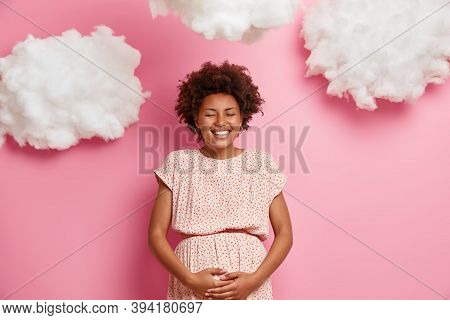 Happy Dark Skinned Pregnant Woman Touches Big Belly, Cares About Future Child, Smiling Expectant Mot