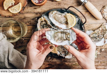 Fresh Oysters With Ice And Lemon On A Rustic Wooden Background.