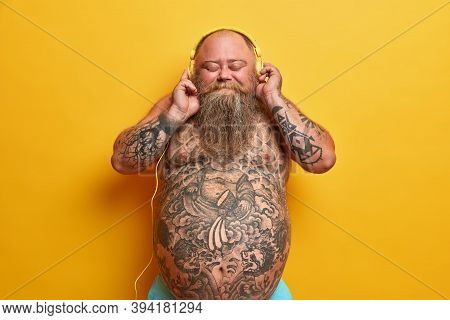 Optimistic Carefree Naked Man With Big Belly, Enjoys Awesome Beat In Stereo Headphones, Closes Eyes,