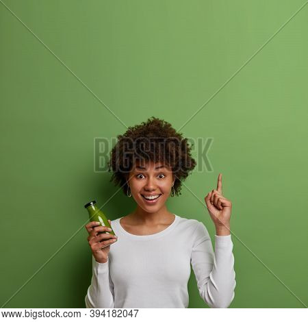 Vertical Shot Of Glad Woman With Natural Afro Hair Holds Bottle Of Freshly Made Smoothie, Points Abo