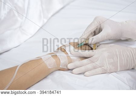 Close Up Doctor's Hand Injects Saline Infusion Needle Into Patient On Bed
