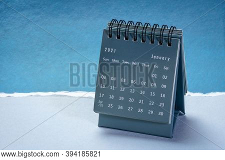 January 2021 - spiral desktop calendar against paper landscape abstract, time and business concept