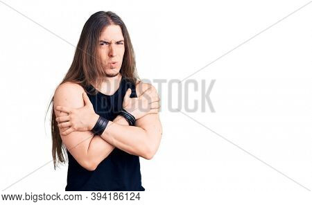 Young adult man with long hair wearing goth style with black clothes shaking and freezing for winter cold with sad and shock expression on face
