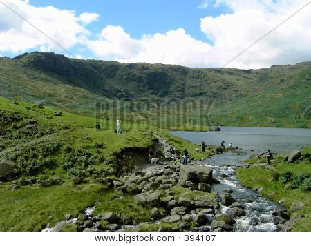 Walkers Resting By A Tarn In The Lake District