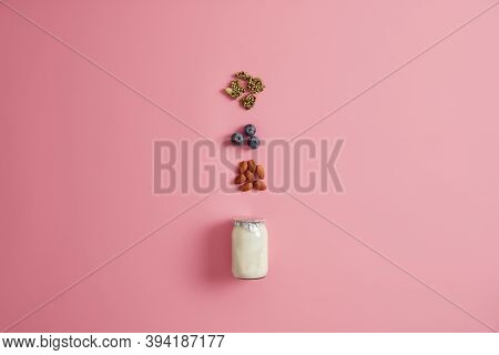 Yoghurt, Pumpkin Seeds, Blueberry And Almond Nut On Pink Studio Background. Ingredients For Healthy
