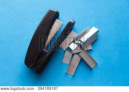 A Set Of Office Supplies Stapler And Staples On Blue Background.