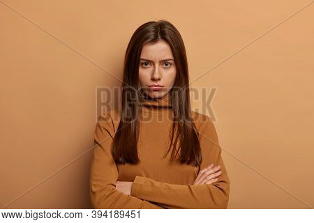 Young Serious Brunette Woman Stands Crossed Arms Indoor, Complains About Being Offended, Displeased