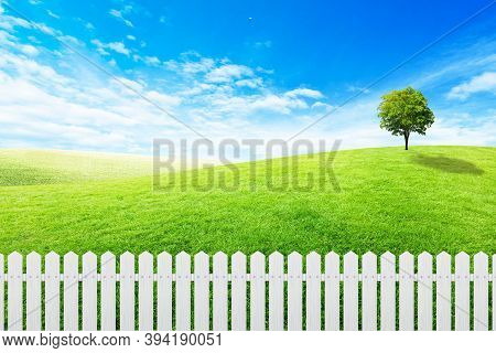 Long White Wooden Fence With Green Grass Meadow Field And Little Hill With White Clouds And Blue Sky