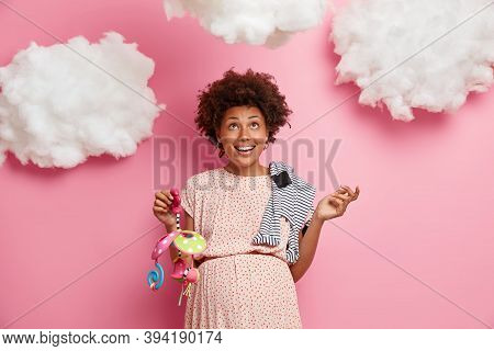 Image Of Happy Pregnant Woman Poses With Baby Mobile And Romper On Shoulder, Cannot Wait For Birth O