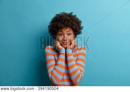 Portrait Of Beautiful Curly Woman With Natural Beauty, Keeps Both Hands Under Chin, Listens Interloc