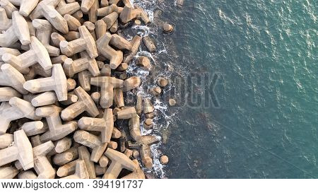 Aerial Drone View Of A Breakwater. Breakwater In The Sea, A Collection Of Concrete Breakers