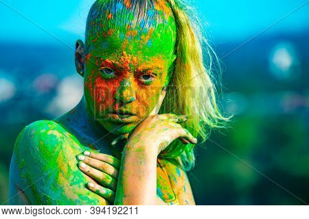 Color Face With Colorful Holi Splash. Cheerful Young Woman With Colorful Paint On Bodies Having Fun