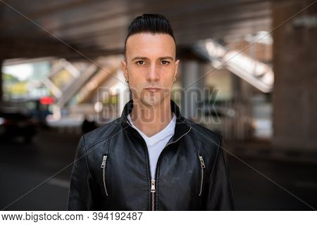 Face Of Handsome Young Italian Man With Undercut Wearing Black Leather Jacket Outdoors