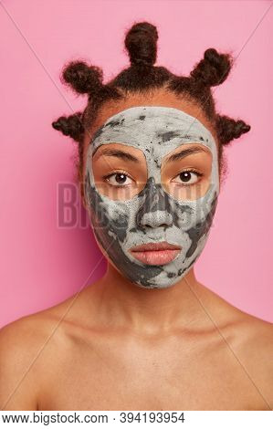 Close Up Shot Of Serious Dark Skinned Woman Applies Beauty Face Mask For Reducing Pores And Blackhea