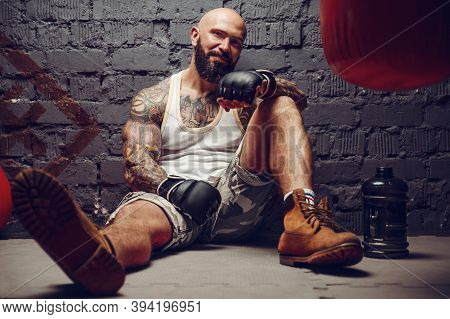 Brutal Tattooed Fighter In Fight Club With Punching Bag